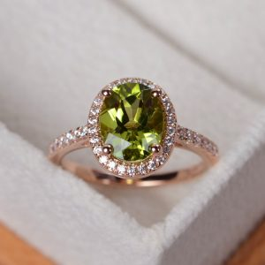 Shop Peridot Rings! Peridot ring, rose gold, halo ring gold, engagement ring rose gold, oval cut, August birthstone ring | Natural genuine Peridot rings, simple unique alternative gemstone engagement rings. #rings #jewelry #bridal #wedding #jewelryaccessories #engagementrings #weddingideas #affiliate #ad