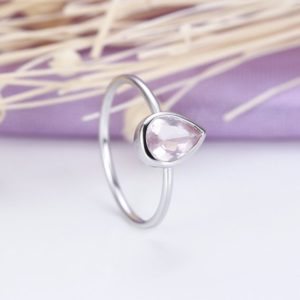Shop Rose Quartz Rings! Solitaire engagement ring for women with a pear shaped rose quartz in white gold Unique Jewelry Promise Simple ring Anniversary gift for her | Natural genuine Rose Quartz rings, simple unique alternative gemstone engagement rings. #rings #jewelry #bridal #wedding #jewelryaccessories #engagementrings #weddingideas #affiliate #ad