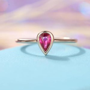 Shop Ruby Rings! Ruby engagement ring Minimalist Delicate Simple Pear shaped cut engagement ring bezel set Thin Dainty Stacking Promise Anniversary gift | Natural genuine Ruby rings, simple unique alternative gemstone engagement rings. #rings #jewelry #bridal #wedding #jewelryaccessories #engagementrings #weddingideas #affiliate #ad