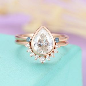 Shop Topaz Engagement Rings! Pear shaped Moissanite engagement ring set Rose gold, Curved London blue topaz  and Diamond wedding band for Women , Anniversary Jewelry | Natural genuine Topaz rings, simple unique alternative gemstone engagement rings. #rings #jewelry #bridal #wedding #jewelryaccessories #engagementrings #weddingideas #affiliate #ad