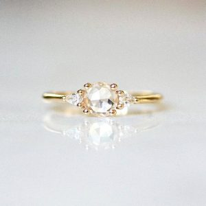 White Sapphire Engagement Ring | 3 Stone Gold Ring | Round Rose Cut Sapphire | Trilogy Engagement Ring | Dainty Engagement [The Maeve Ring] | Natural genuine Gemstone rings, simple unique alternative gemstone engagement rings. #rings #jewelry #bridal #wedding #jewelryaccessories #engagementrings #weddingideas #affiliate #ad