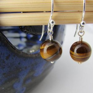 Shop Tiger Eye Jewelry! Tiger Eye Earrings, small dangle earrings, round tigers eye, tiger iron stone earrings | Natural genuine Tiger Eye jewelry. Buy crystal jewelry, handmade handcrafted artisan jewelry for women.  Unique handmade gift ideas. #jewelry #beadedjewelry #beadedjewelry #gift #shopping #handmadejewelry #fashion #style #product #jewelry #affiliate #ad