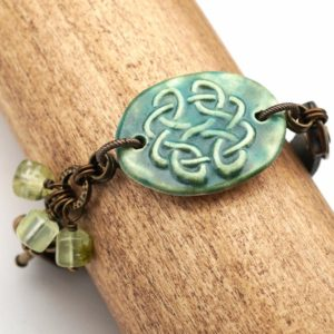 Shop Prehnite Bracelets! Green Celtic Knot Bracelet, Ceramic Leather Brass, Prehnite Beads, 7 3 / 4 Inches Long, Fits 6 1 / 2 Inch Wrist | Natural genuine Prehnite bracelets. Buy crystal jewelry, handmade handcrafted artisan jewelry for women.  Unique handmade gift ideas. #jewelry #beadedbracelets #beadedjewelry #gift #shopping #handmadejewelry #fashion #style #product #bracelets #affiliate #ad