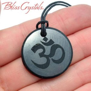 Shop Shungite Pendants! Shungite OM Round Pendant w/ Cord for protection from EMF Healing Crystal and Stone #SP68 | Natural genuine Shungite pendants. Buy crystal jewelry, handmade handcrafted artisan jewelry for women.  Unique handmade gift ideas. #jewelry #beadedpendants #beadedjewelry #gift #shopping #handmadejewelry #fashion #style #product #pendants #affiliate #ad