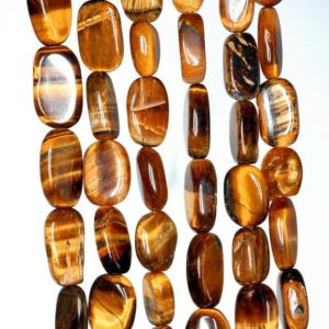 Shop Tiger Eye Chip & Nugget Beads! 8×6-15x8mm Cognac Tiger Eye Gemstone Yellow Pebble Nugget Loose Beads 13-14 inch Full Strand (90184982-898) | Natural genuine chip Tiger Eye beads for beading and jewelry making.  #jewelry #beads #beadedjewelry #diyjewelry #jewelrymaking #beadstore #beading #affiliate #ad