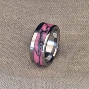 Shop Rhodonite Rings! Titanium Ring inlaid with off center Rhodonite TruStone.  Wedding Band, Rhodonite ring, Pink ring, Handmade ring. | Natural genuine Rhodonite rings, simple unique alternative gemstone engagement rings. #rings #jewelry #bridal #wedding #jewelryaccessories #engagementrings #weddingideas #affiliate #ad