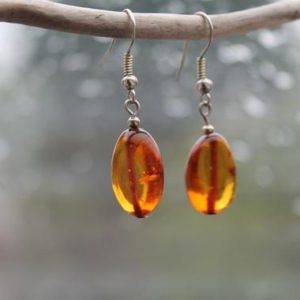 Shop Amber Earrings! Baltic Amber Earrings Dangle Orange Oval Amber Jewelry Transparent Dangling Slow Fashion Handcrafted Amber | Natural genuine Amber earrings. Buy crystal jewelry, handmade handcrafted artisan jewelry for women.  Unique handmade gift ideas. #jewelry #beadedearrings #beadedjewelry #gift #shopping #handmadejewelry #fashion #style #product #earrings #affiliate #ad
