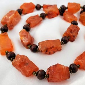 Shop Carnelian Necklaces! Chunky, boho carnelian necklace with wood, & brass beads. Red orange autumn colored luminous stones. Hand-knapped stones | Natural genuine Carnelian necklaces. Buy crystal jewelry, handmade handcrafted artisan jewelry for women.  Unique handmade gift ideas. #jewelry #beadednecklaces #beadedjewelry #gift #shopping #handmadejewelry #fashion #style #product #necklaces #affiliate #ad