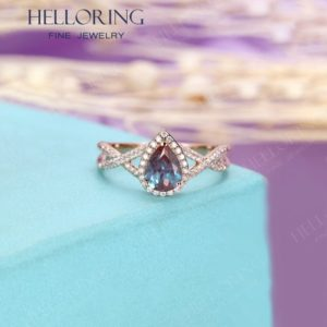 Shop Alexandrite Rings! Alexandrite engagement ring rose gold,Pear shaped ring ,Halo set half eternity diamond/moissanite ,Anniversary  Twisted band | Natural genuine Alexandrite rings, simple unique alternative gemstone engagement rings. #rings #jewelry #bridal #wedding #jewelryaccessories #engagementrings #weddingideas #affiliate #ad