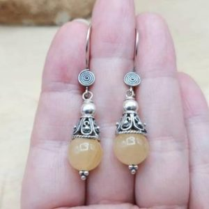 Shop Aragonite Earrings! Aragonite cone earrings. Bali bead earrings. Capricorn Reiki jewelry uk. Yellow rare mineral dangle drop Wire wrap earrings   Natural genuine Aragonite earrings. Buy crystal jewelry, handmade handcrafted artisan jewelry for women.  Unique handmade gift ideas. #jewelry #beadedearrings #beadedjewelry #gift #shopping #handmadejewelry #fashion #style #product #earrings #affiliate #ad