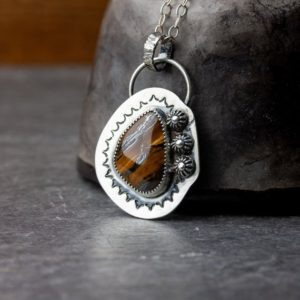 Shop Tiger Iron Pendants! Black Sun | Tiger iron pendant with sterling silver accents | Tiger's Eye sterling silver necklace | Natural genuine Tiger Iron pendants. Buy crystal jewelry, handmade handcrafted artisan jewelry for women.  Unique handmade gift ideas. #jewelry #beadedpendants #beadedjewelry #gift #shopping #handmadejewelry #fashion #style #product #pendants #affiliate #ad