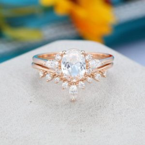 Shop Sapphire Rings! Oval white sapphire engagement ring set Unique Cluster Rose gold engagement ring Curved diamond Bridal promise Anniversary gift for her | Natural genuine Sapphire rings, simple unique alternative gemstone engagement rings. #rings #jewelry #bridal #wedding #jewelryaccessories #engagementrings #weddingideas #affiliate #ad