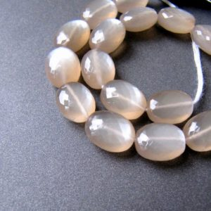 Shop Moonstone Chip & Nugget Beads! Coffee Moonstone ovals • Pairs available • 10-10.75mm • AAA+ Selected Micro faceted nuggets • Natural gemstone • Beige with silver moon glow | Natural genuine chip Moonstone beads for beading and jewelry making.  #jewelry #beads #beadedjewelry #diyjewelry #jewelrymaking #beadstore #beading #affiliate #ad